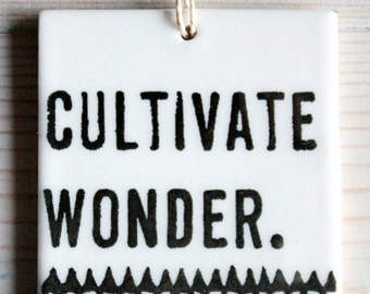 porcelain wall tag screenprinted text cultivate wonder and hand drawn triangle pattern.