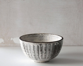 Handmade white and dark brown carved ceramic bowl with foot
