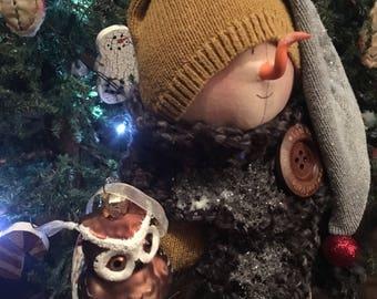 Snowman holding a glass owl ornament