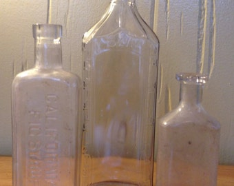 ANTIQUE APOTHECARY BOTTLES Set of Three Antique Glass Bottles including a California Fig Syrup Co & Blue BBon Bottles