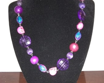 Purple Beaded Necklace with Pink Skulls made of Glass.
