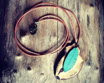 Neklace with wood pendant and feather