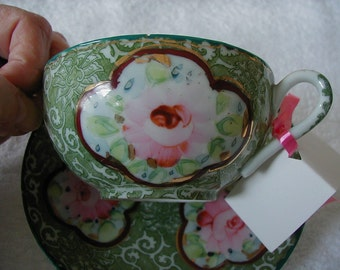 Very decorative pink and green cup and saucer