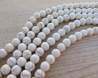 Set of 25 8mm in diameter synthetic howlite freshwater white pearls.