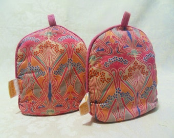A pair of Liberty of London pink egg cosies in the Ianthe design