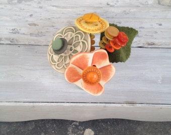 orange, sage green, and yellow button flower bottle bouquet