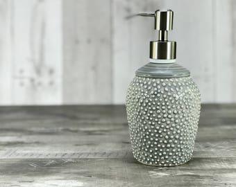 Grey soap dispenser. Porcelain soap dispenser. Ceramic soap dispenser. Grey bathroom. Gray bathroom. Textured pattern. Brushed nickel pump.