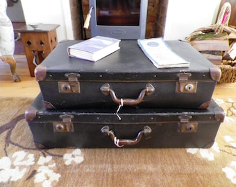 A Pair of 1930s Vintage Wooden Framed Fibre graduated suitcases in black luggage travel prop