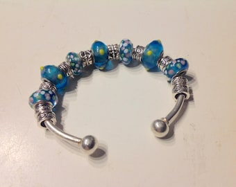 Sterling silver cuff bracelet with turquoise lampwork and silver beads.