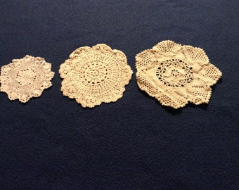 Three vintage thread crochet doilies, smaller sizes, done with an off-white ecru thread color.