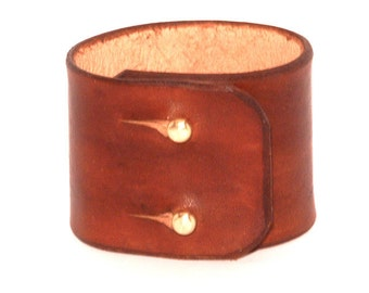 Wide leather bracelet with a brass ball closure