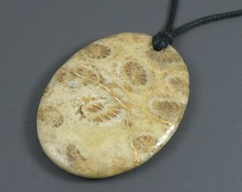 Kintsugi (kintsukuroi) fossilized coral oval stone pendant with gold repair on cotton cord - OOAK