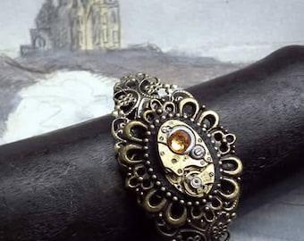 Ajustable filigree steampunk bracelet :  framed mechanism, black resin, yellow swarovski crystal cab, watch cogs