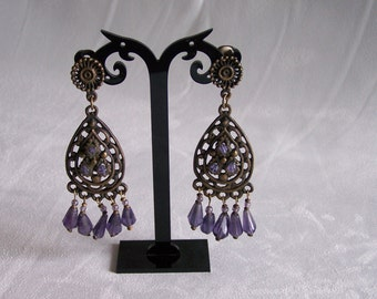 Earrings clip in patinated bronze filigree and purple glass beads