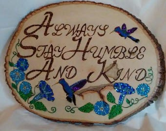 Always Stay Humble and Kind with flowers and humming birds, wood burned wall decor.  Painted and embellished with colored crystals.