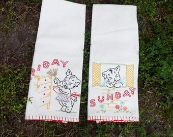 Great pair of red side striped heavier cotton tea towels - hand embroidered - black dog cleaning and relaxing - Sunday and Friday