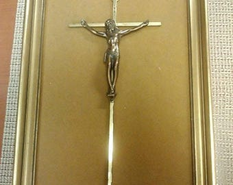Gold framed crucifix on a brown velvet background from Early 1900s
