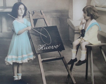 postcard of two children playing teacher and pupil, vintage postcard