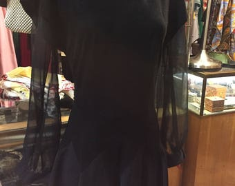 Wonderfully structured dress of the 1950s in black with delightful sheer sleeves