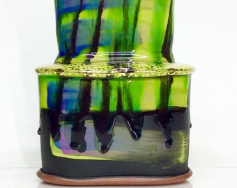 bright green and black vase with gold dots and glaze drips