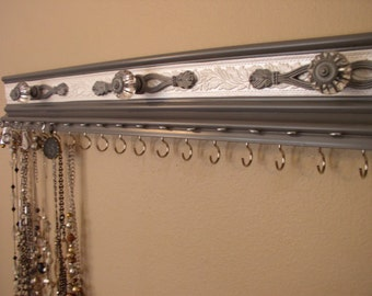 Jewelry organizer for both necklaces and earrings in gray. This wall rack is both functional and pretty, with  19 hooks