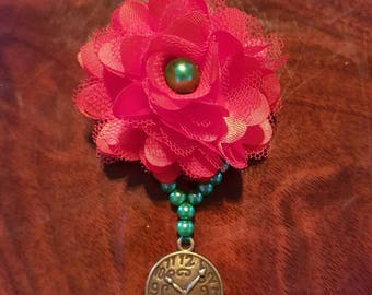 Small red flower hair fascinator with a brass clock face pendant on a green pearl drop