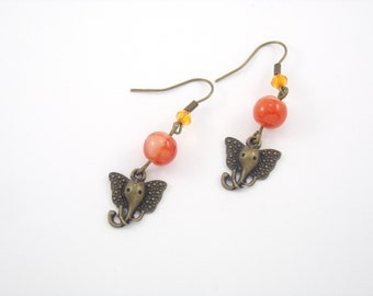 Earrings bronze metal, with its marbled orange glass bead and is in the shape of elephant head charm
