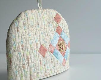 Quilted patchwork tea cozy of very gentle colour, Beige tea cozy with cross motif