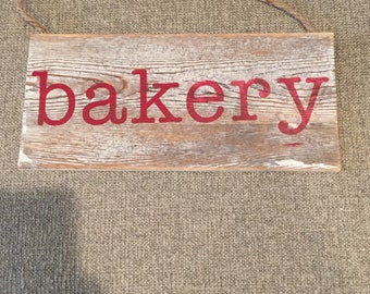 """White wash sign with red lettering""""bakery"""" sign"""