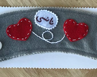 Personalized heart coffee cup sleeve with buttons, on gray background.
