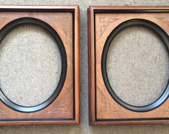 Pair Victorian walnut frames, oval openings, incise carving with ebonized highlights