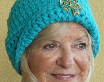 Aqua winter hat with a jeweled bauble, whimsical crochet hat with great class, much like a flapper hat in style and fun, versatile style