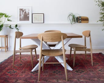 Custom recycled timber dining table with splayed steel legs