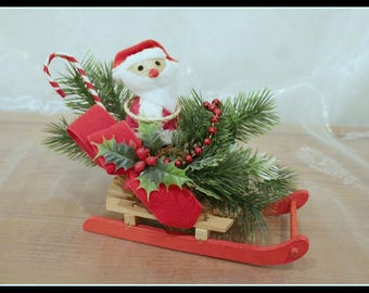 Classic Santa Claus On An Evergreen Covered Sled, Vintage Santa Claus Sled With Evergreen Leaves Red Ribbons Pine Cones and a Candy Cane