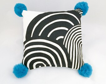 Small screen-printed cushion with teal pompoms