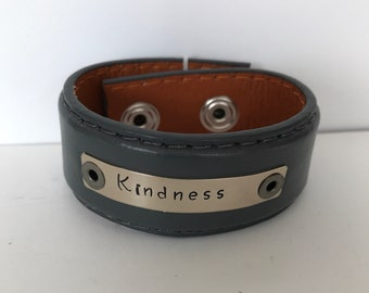 "Gray leather upcycled belt bracelet with a handstamped message on silver blank.  Message reads,""kindness"""