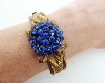 Art Deco open work filigree bangle bracelet with blue paste cluster and floral detail