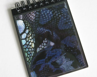 "Alexander McQueen A7 (11x8cm) spiral-bound notebook made with ""Black Snake' print paper."