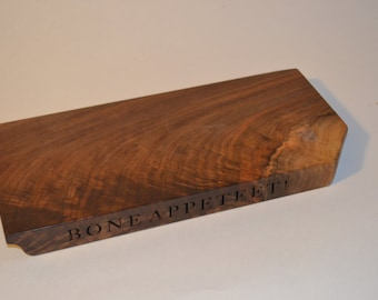 BONE APPETEET! is laser engraved on one edge of a 12 3/8 x 5 3/4 x 1 inch Oregon black walnut slab