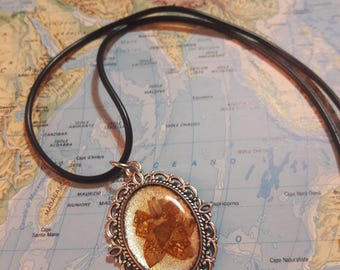 Necklace with metal base pendant and resin cabochon with flower inside