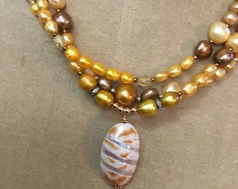 Handcrafted triple strand necklace with shell pendant -- gold and brown necklace