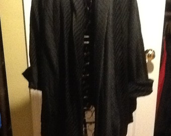 Black swing coat 1950's. Ribbed all over. Wide cuff sleeve. Size small to medium.