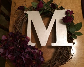 Decorative hanging wreaths with personalized letter and flowers.