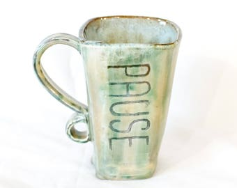 "Hand-built mug with a creamy white glaze and carved word ""PAUSE."""
