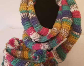 A handmade, multi-coloured, extremely long, crochet skinny scarf with Pom Poms