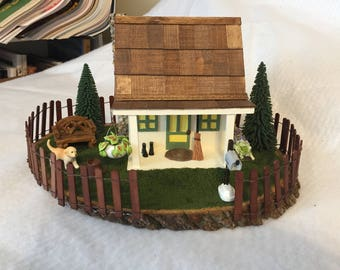 Diorama of house with yard and Labrador puppy.