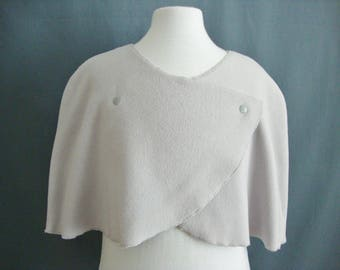 Grey fleece mini cape closed with clear silver snaps.