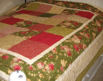 Roses theme this F/Q Quilt in reds, greens, golds bright colors.  Back in gold all over, long arm maching quilting in random leaf pattern.