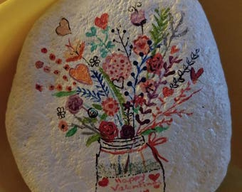 Happy valentine flower vase painted on a rock.