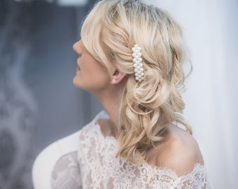 A hair piece, attached to a comb, a beautiful application with pearls and crystals.